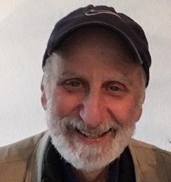 Guy Sussman, a white man with a white beard,  smiling, facing the camera in a baseball cap. He is wearing a tan jacket with a black shirt.